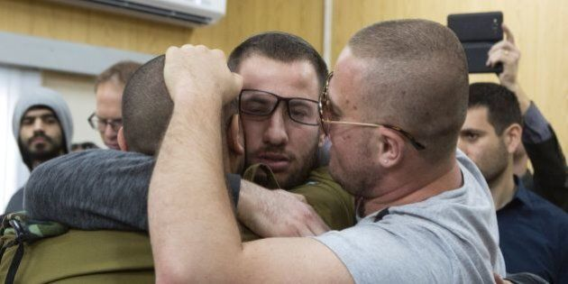 Israeli soldier Elor Azaria (L), who shot dead a wounded Palestinian assailant in March 2016, is embraced...