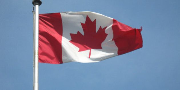 A Canadian flag blowing in the wind on a perfect