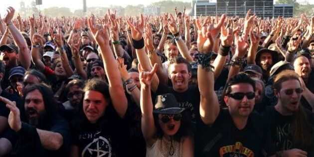 Festival goers gestures as they attend the Hellfest heavy metal and hard rock music festival in Clisson...
