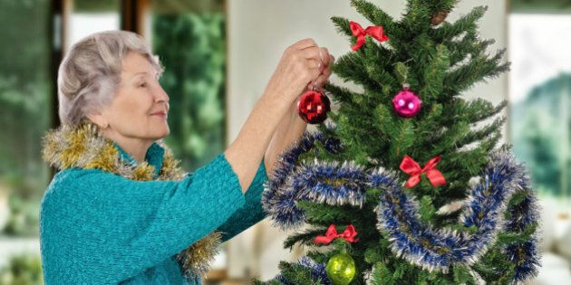 Stunning old woman in turquoise sweater hangs on Christmas tree a red ball. Standing sideways gray-haired...
