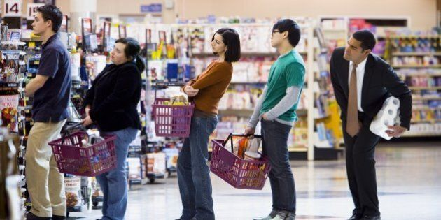 People waiting in line with shopping baskets at grocery