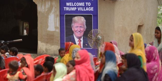 Indian women gather to listen to a speaker next to a poster with the image of US President Donald Trump...