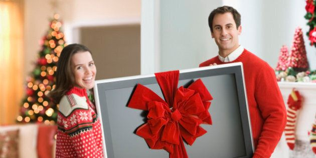 Couple holding flat screen TV with ribbon round it at