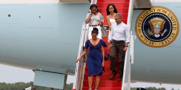 U.S. President Barack Obama and his family arrive aboard Air Force One in transit to their annual summer...