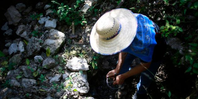 A man with a missing relatives uses a metal rebar to search in an area containing mass graves in Cerro...