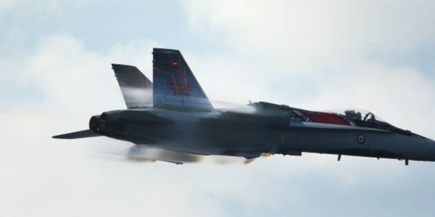 TORONTO, ON- SEPTEMBER 1 - The CF-18 Hornet generates vapour as it climbs races by the grandstand at...