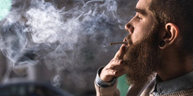Close up of hipster man smoking weed