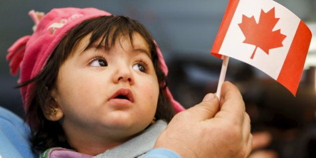 A young Syrian refugee looks up as her father holds her and a Canadian flag at the as they arrive at...