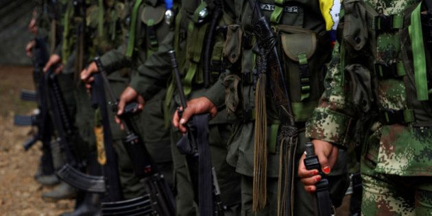 FARC members stand during a formation in a camp before moving to the transitional zone of Pueblo Nuevo,...