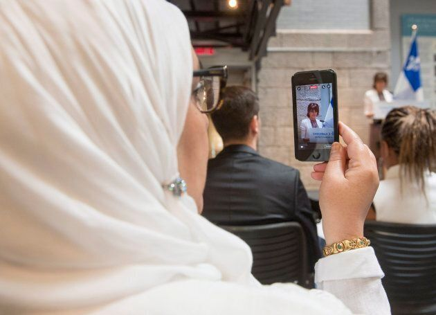 A woman records on her phone as Quebec Immigration, Diversity and Inclusiveness Minister Kathleen Weil makes an announcement about the fight against systemic discrimination and racism on July 20, 2017 in Montreal.THE CANADIAN PRESS/Ryan Remiorz