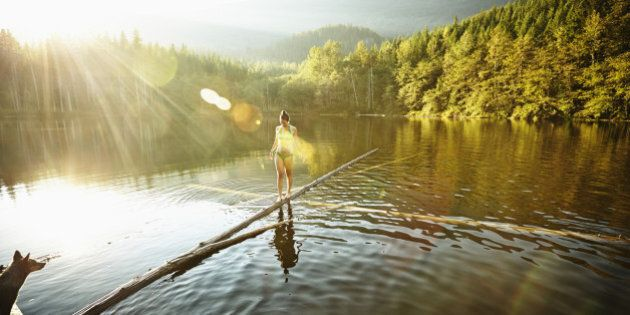 Woman walking on log in alpine lake with dog watching from dock