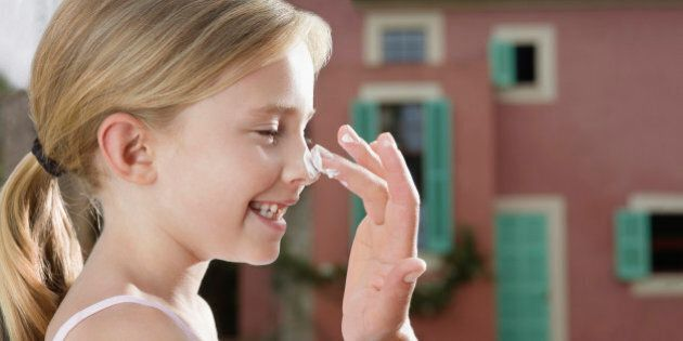 Mother applying sunscreen to daughter's (5-6) nose side view close-up of