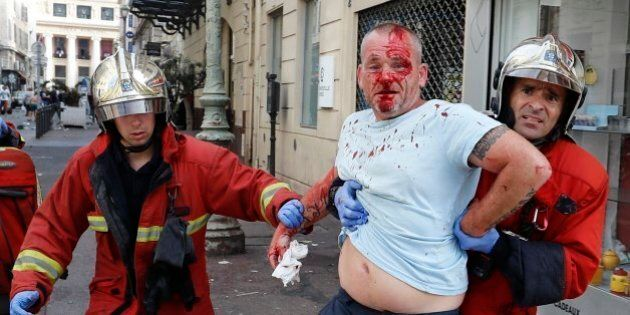 A man is taken away by emergency service workers after he was injured in clashes in downtown Marseille,...
