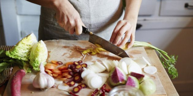 Woman cooking in kitchen with ingredients around