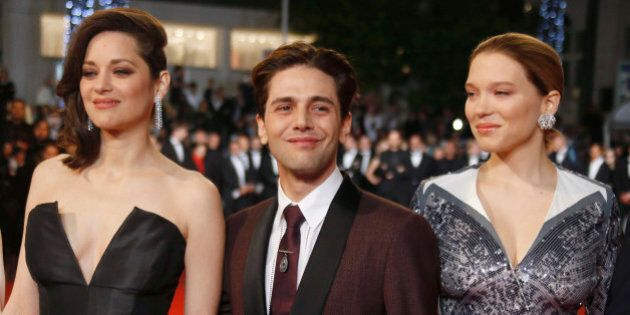 Director Xavier Dolan (C), cast members Lea Seydoux (R) and Marion Cotillard pose on the red carpet as...