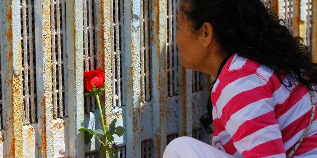 Une femme souligne la fête des Mères devant la frontière entre les États-Unis et le Mexique. Tijuana,...