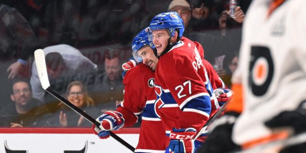 MONTREAL, QC - FEBRUARY 10: Tomas Plekanec #14 celebrates with Alex Galchenyuk #27 of the Montreal Canadiens...