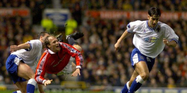 Manchester United's Dutch player Jordi Cruyff (2L) is tackled by first division club Bury's Dean Barrick...