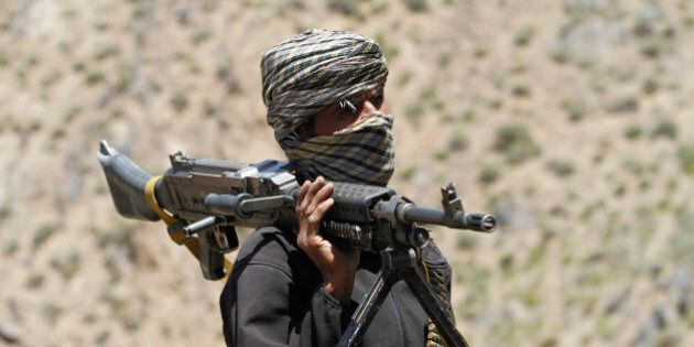 FILE - In this May 27, 2016 file photo, a member of a breakaway faction of the Taliban fighters guards...