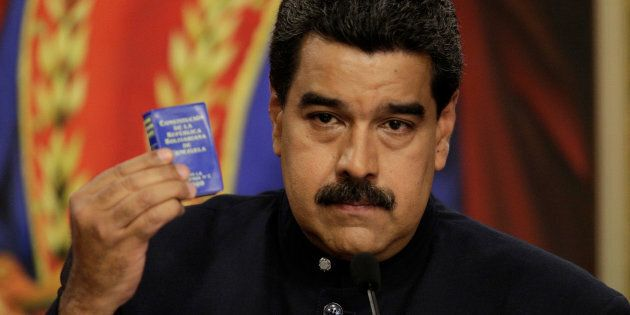 Venezuela's President Nicolas Maduro holds up a book of the country's constitution during a news conference...