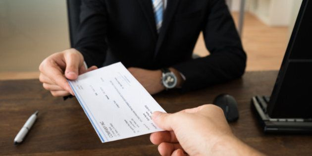 Close-up Of Businessman Hands Giving Cheque To Other Person In