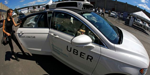 A journalist gets in a self driving Uber for a ride during a media preview at Uber's Advanced Technologies...