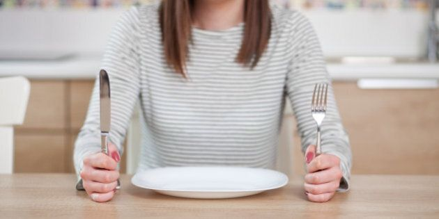 Displeased young woman sitting at the empty plate. Shallow depth of field, focus on