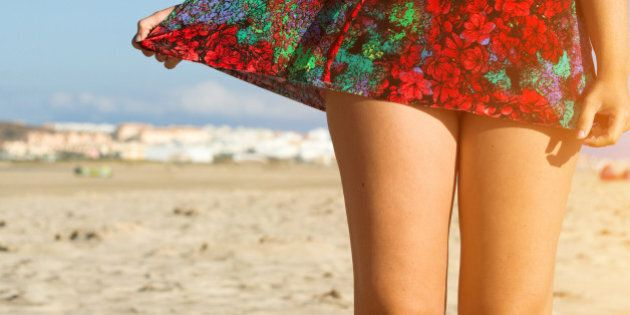 The bare legs of a woman, her hand clutching her colorful dress on the beach in Cadiz,