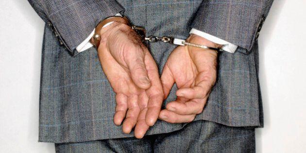 Businessman in handcuffs,rear