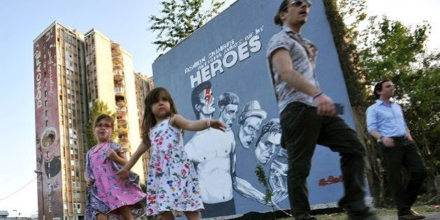 Bosnian children dance in front of the mural painting of David Bowie during the unveiling ceremony in...