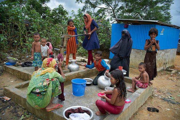 Des femmes et des enfants sont rassemblés au point d'eau afin de se laver, de faire la lessive et de...