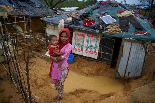Zohra tient sa soeur âgée de deux ans, devant leur abri improvisé au camp de fortune Kutupalong pour...