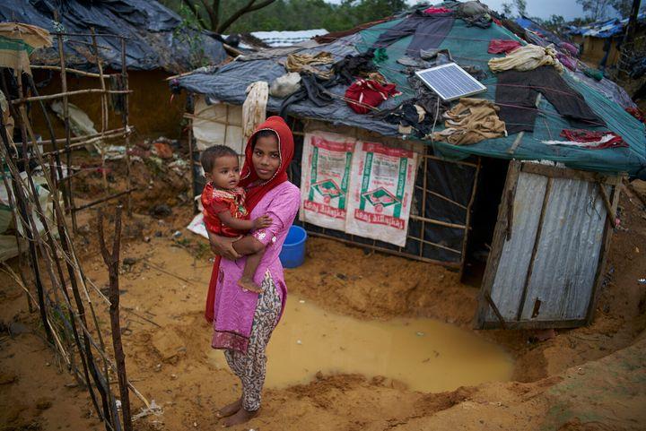 Zohra tient sa soeur âgée de deux ans, devant leur abri improvisé au camp de fortune Kutupalong pour personnes réfugiées rohingyas, au Bangladesh.