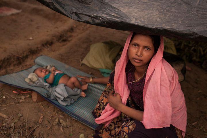Des familles de réfugiés rohingyas s'apprêtent à construire un abri improvisé au camp de fortune Kutupalong pour personnes réfugiées rohingyas, au Bangladesh.