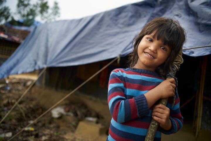 Une jeune fille rohingya sourit devant l'abri de fortune de sa famille au camp de fortune Balukhali pour personnes réfugiées rohingyas, au Bangladesh.