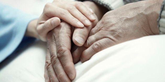 Hand of woman touching senior man in