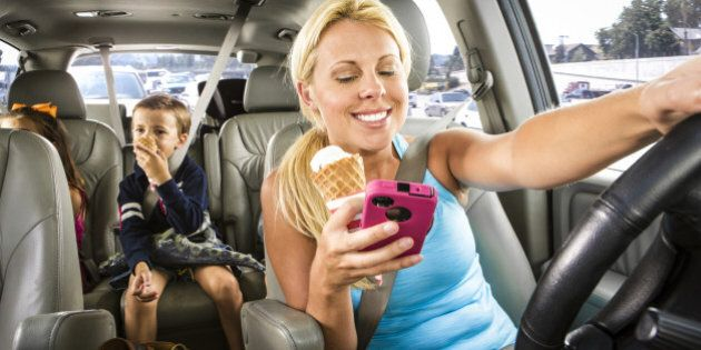 Soccer mom reads a text and eats an ice cream while driving her kids in minivan