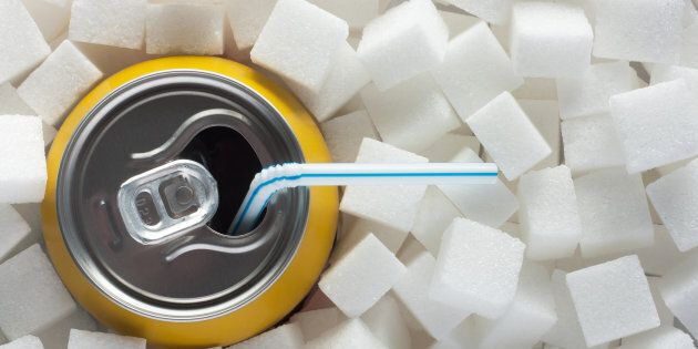 Unhealthy food concept - sugar in carbonated drink. Sugar cubes as background and canned drink