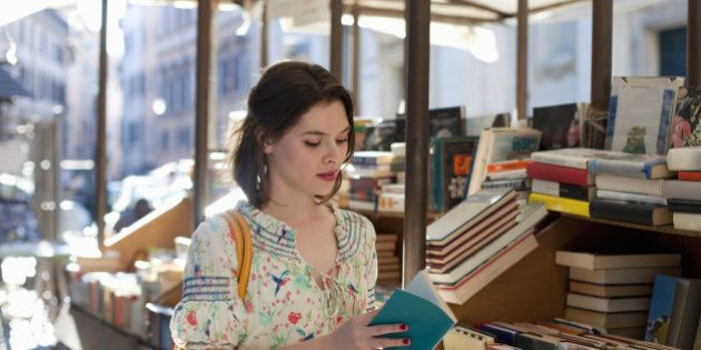 young woman flipping through book at