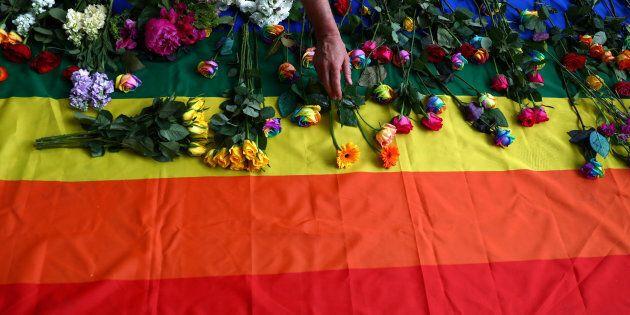 Des manifestants déposent des fleurs sur un drapeau arc-en-ciel alors qu'ils manifestent pour les droits...