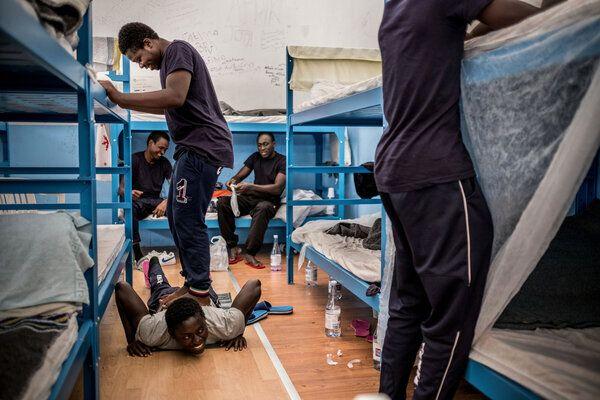 Abdullah, un jeune Gambien âgé de 15 ans (debout), aide son ami Alieu, âgé de 17 ans (au centre, étendu sur le plancher), à soulager ses douleurs au dos, dans un centre de réception pour les demandeurs d'asile qui sert également de centre d'hébergement pour les mineurs non-accompagnés, dans le port de Pozzallo, Sicile, en Italie (Mai 2016).