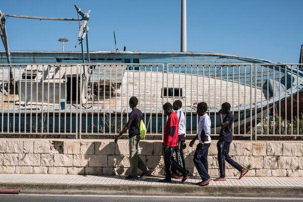 De jeunes Gambiens passent près d'un bateau de contrebande dans un cimetière de navires, dans le port près du centre de réception pour les demandeurs d'asile qui sert également de centre d'hébergement pour les mineurs non-accompagnés à Pozzallo, en Sicile, en Italie (Mai 2016).