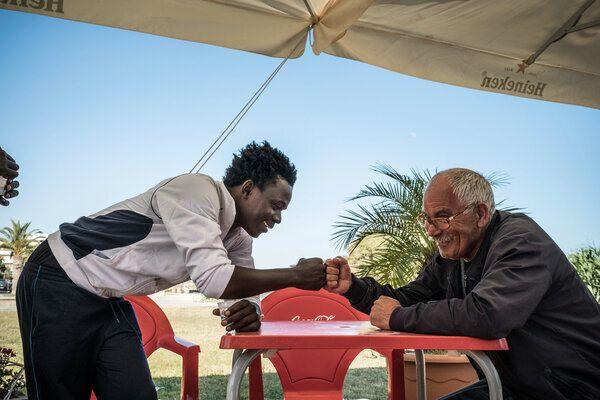 Mohammad, âgé de 17 ans, sympathise avec un Italien, lors d'une sortie du centre de réception pour les demandeurs d'asile qui sert également de centre d'hébergement pour les mineurs non-accompagnés, dans le port de Pozzallo, Sicile, en Italie (Mai 2016).