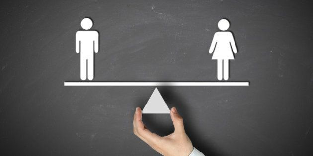 Male equals female concept with businessman hand holding against blackboard background.