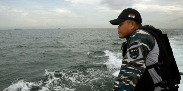 A navy personnel looks for survivors during a search and rescue operation after a boat carrying Indonesian...