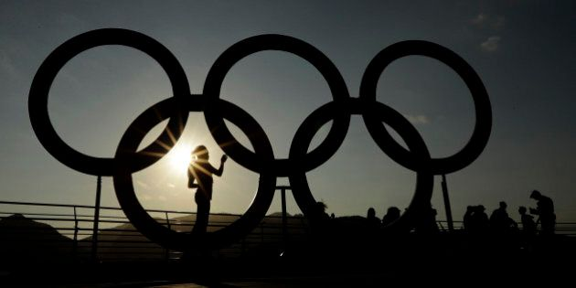 A woman is silhouetted by the setting sun as she looks at a set of Olympic rings in the Olympic Park...