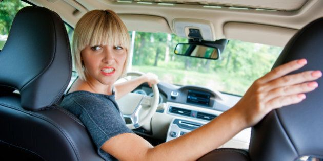 attractive woman driver looking back and parking car