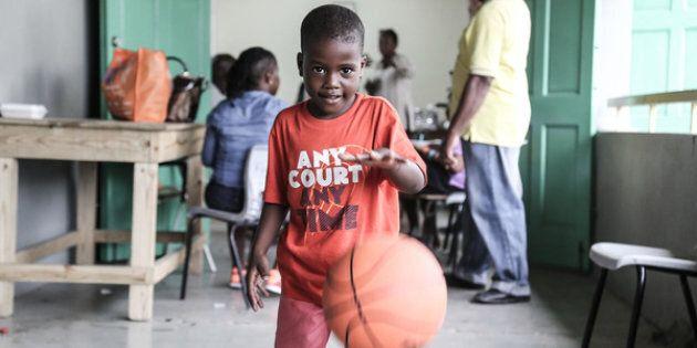 Un jeune garçon joue avec un ballon qu'il vient de recevoir au centre de distribution de l'UNICEF, à...