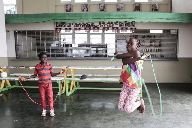 Desre Simon et son frère Unique Simon sautent à la corde, après avoir reçu du matériel récréatif, à Saint John's, à Antigua.