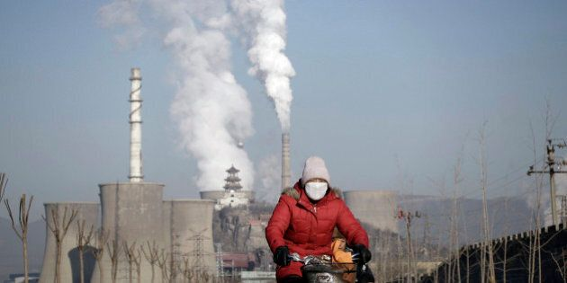 A woman wearing a mask rides past smoking chimneys and cooling towers of a steel plant in Beijing, January...